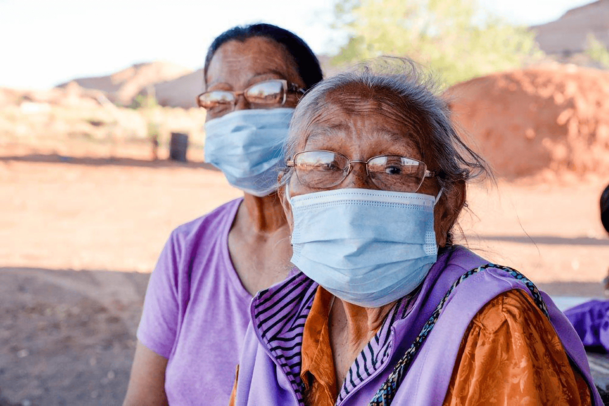 An elderly indigenous woman and a middle-aged indigenous woman both wearing glasses and masks sitting together outside in a dessert environment.