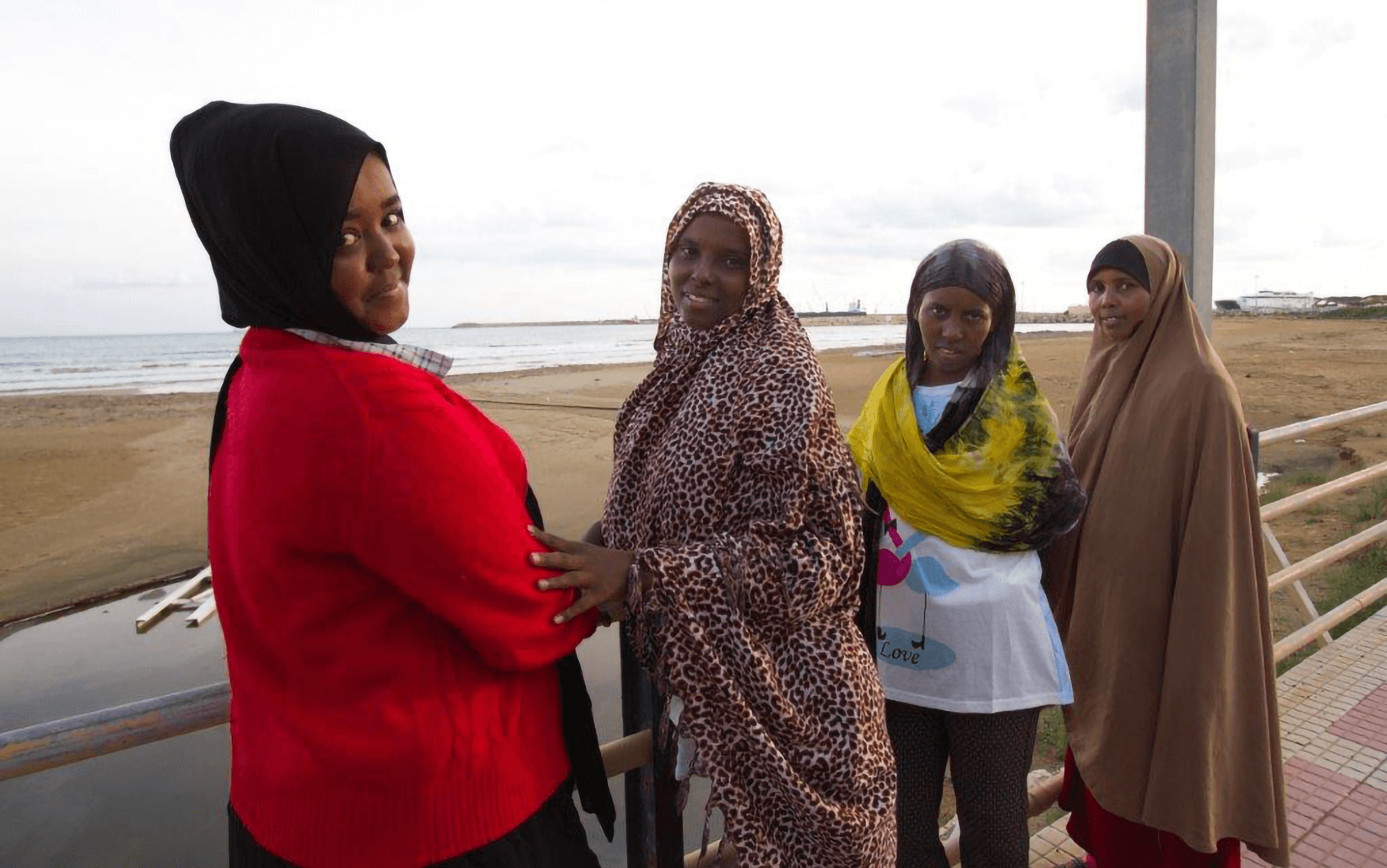 Four female Muslim women wearing hijabs standing on a boardwalk by the ocean, looking back and smiling.