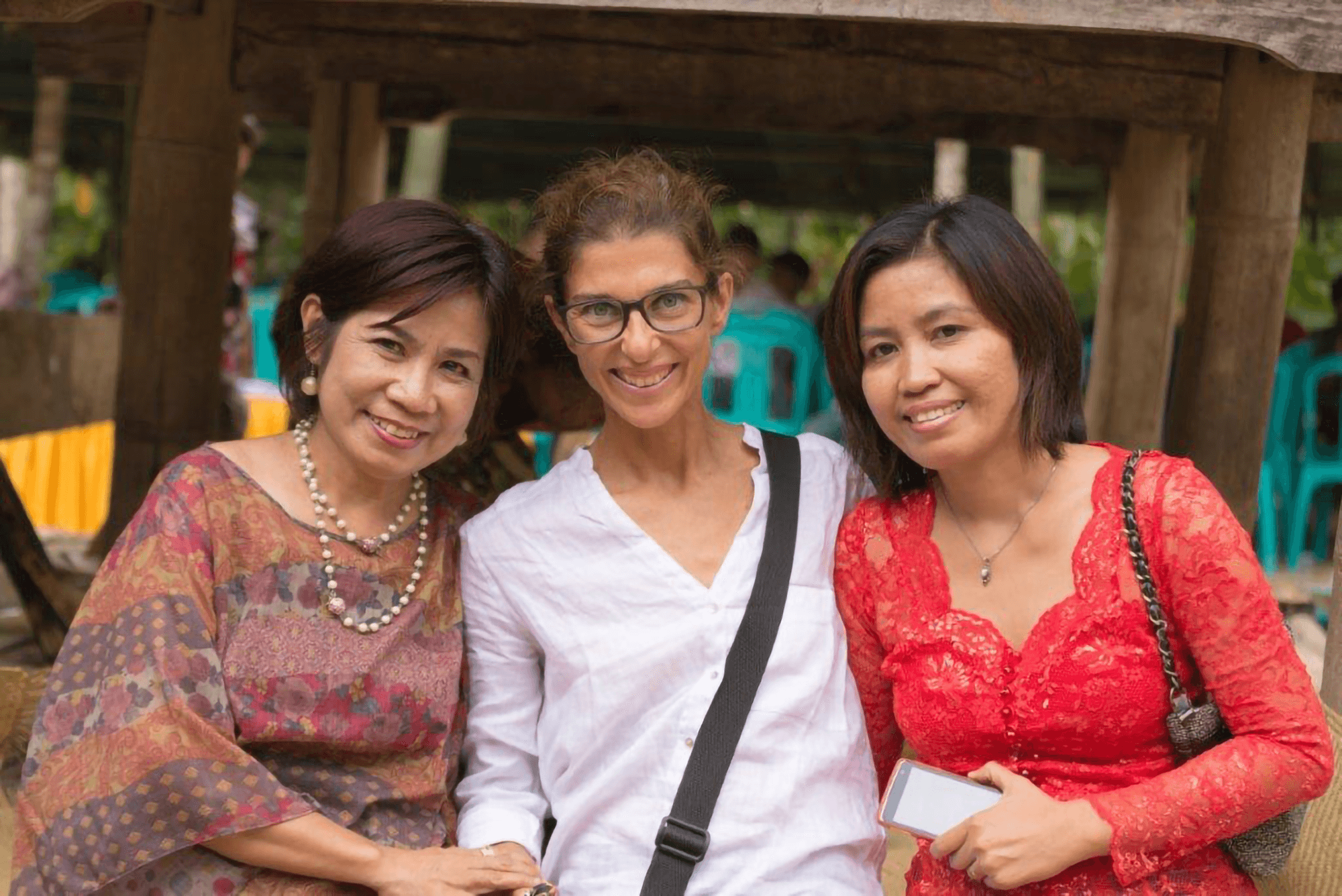 Three multiracial middle-aged women standing together and smiling.